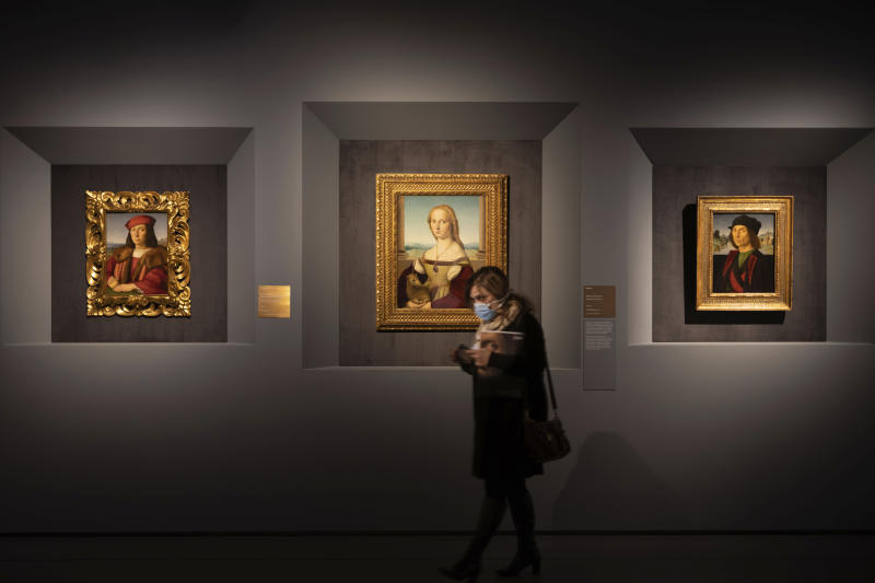 A woman wearing a mask walks past, from left, Raphael's portrait of a Young Man with an Apple, Young Woman with Unicorn and Portrait of a Man, at a press preview of Raphael's exhibition in Rome, Wednesday, March 4, 2020. The paintings,  drawings and sketches in the most ambitious assemblage ever of Raphael works in an exhibition, more than even the Renaissance superstar had in his workshop at one time, are collectively insured for 4 billion euros ($.4 billion), against the likes of theft or vandalism. But no money can guarantee that Italy's outbreak of coronavirus, the largest in Europe, won't play havoc with the three-month run in Rome of the art world's eagerly-awaited blockbuster. (AP Photo/Domenico Stinellis)