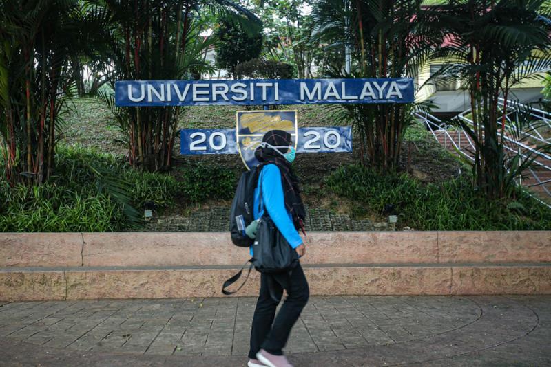 A student walks past the Universiti Malaya signage March 17, 2020. — Picture by Hari Anggara