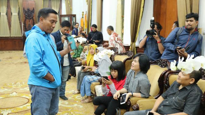Orangtua mahasiswa Unesa memantau perkembangan anak-anaknya di Natuna melalui media massa. (Liputan6.com/ Dian Kurniawan)