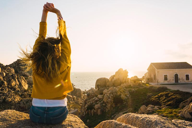 Italy, Sardinia, woman on a hiking trip sitting on rock at the coast raising her arms