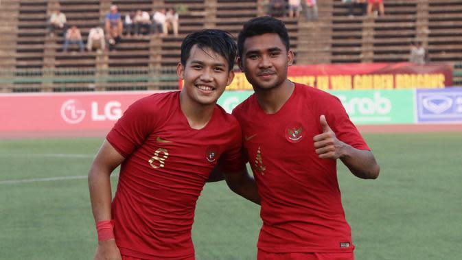 Pemain Timnas Indonesia U-22, Witan Sulaeman, merayakan kemenangan bersama Asnawi Mangkualam pada laga Piala AFF U-22 2019 di Olympic Stadium, Phnom Penh, Kamboja, Minggu (24/2/2019). Indonesia menang 1-0 atas Vietnam. (Bola.com/Zulfirdaus Harahap)