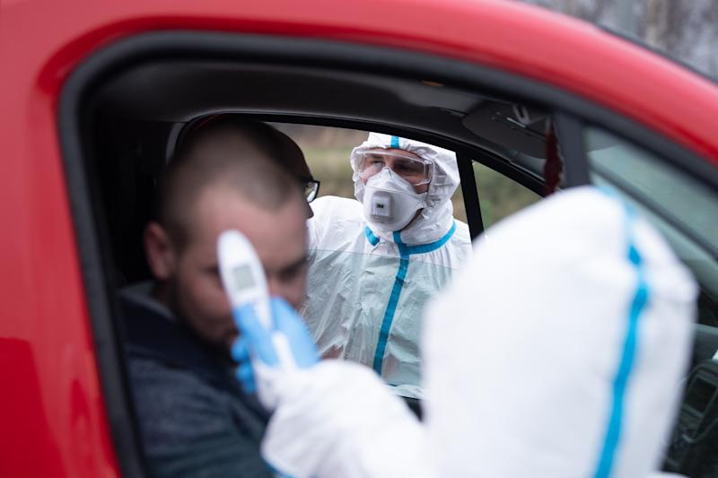 09 March 2020, Poland, Jedrzychowice: Two members of the Polish Rescue Service, wearing protective clothing, are checking the body temperature of two men at a border checkpoint of the Lower Silesia Voivodeship Police on the Polish-German border using a thermometer. On the same day, checks are carried out at several points along the border to prevent the corona virus from spreading. Thus, the authorities draw the consequences from the first case of Covid-19 disease detected in Poland. Photo: Sebastian Kahnert/dpa-Zentralbild/dpa (Photo by Sebastian Kahnert/picture alliance via Getty Images)