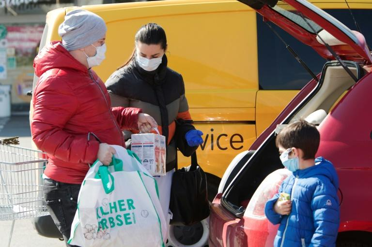 A family ensure they have their masks on as they put shopping in the car in Brunn am Gebirge near Vienna