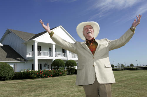 "FILE - In this Oct. 9, 2008 file photo, actor Larry Hagman poses in front of the Southfork Ranch mansion in Parker, Texas made famous in the television show ""Dallas."" Actor Larry Hagman, who for more than a decade played villainous patriarch JR Ewing in the TV soap Dallas, has died at the age of 81, his family said Saturday Nov. 24, 2012. (AP Photo/Tony Gutierrez, File)"