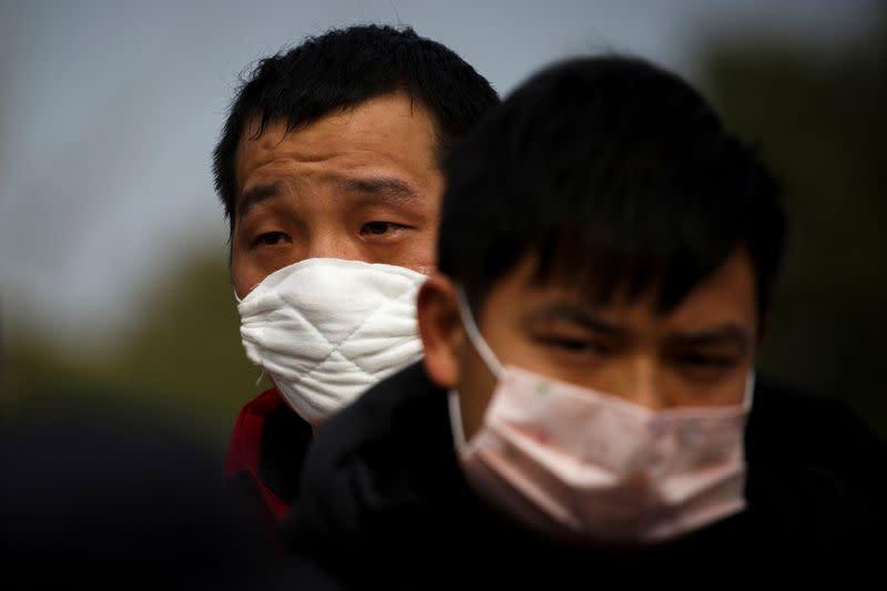 FILE PHOTO: People coming from the Hubei province wait at a checkpoint at the Jiujiang Yangtze River Bridge in Jiujiang
