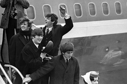 FILE - Britain's Beatles make a windswept arrival in New York in this Feb. 7, 1964 file photo, as they step down from the plane that brought them from London, at Kennedy airport. From left to right, Ringo Starr, John Lennon, Paul McCartney and George Harrison. One of the most tumultuous welcomes in pop history is to be recreated next month when UK officials and a tribute band recreate the Beatles' historic 1964 landing at JFK airport, in a bid to spark interest in Beatles-related tourism to Britain. (AP Photo, File)
