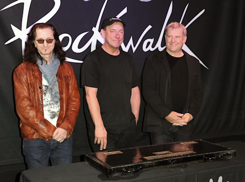 """FILE - This Nov. 20, 2012 file photo shows members of the band Rush, from left, Geddy Lee, Neil Peart, and Alex Lifeson at the RockWalk induction of Rush at Guitar Center in Los Angeles. The eclectic group of rockers Rush and Heart, rappers Public Enemy, songwriter Randy Newman, """"Queen of Disco"""" Donna Summer and bluesman Albert King will be inducted into the Rock and Roll Hall of Fame next April in Los Angeles. The inductees were announced Tuesday by 2012 inductee Flea of The Red Hot Chili Peppers at a news conference in Los Angeles. (Photo by Richard Shotwell/Invision/AP, file)"""