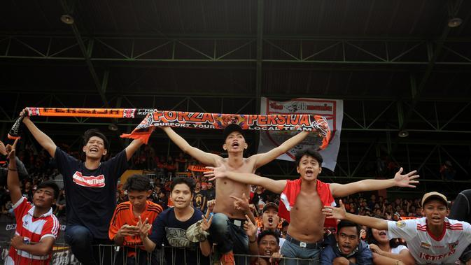 Suporter tim Macan Kemayoran meneriakkan yel yel saat menyaksikan laga uji coba antara Persija melawan Barito Putera di Stadion Bea Cukai Rawamangun, Jakarta, Selasa (5/4/2016). Laga uji coba berakhir imbang 2-2. (Liputan6.com/Helmi Fithriansyah)