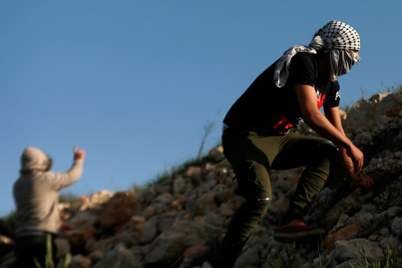 A Palestinian demonstrator takes cover from Israeli forces during a protest against Israeli settlements, near the town of Beita in the Israeli-occupied West Bank