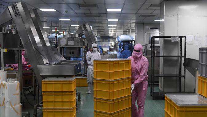 Seorang pekerja mendorong peti di dekat jalur produksi di pabrik Jarum Suntik Hindustan di Faridabad (2/9/2020). Produksi jarum suntik ditingkatkan mengantisipasi lonjakan permintaan saat perlombaan global untuk menemukan vaksin virus corona COVID-19 memanas. (AFP/Sajjad Hussain)