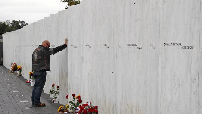 File foto 11 September 2018 ini, seorang pengunjung Flight 93 National Memorial di Shanksville, Pa., Memberi penghormatan di Wall of Names setelah Service of Remembrance, saat negara tersebut menandai peringatan 17 tahun peringatan Serangan 11 September 2001. (AP Photo/Gene J. Puskar)