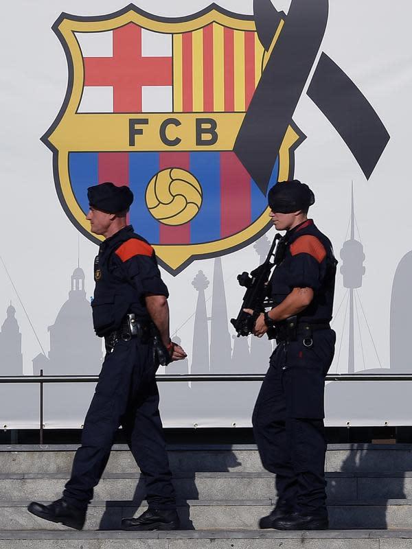 Polisi melintasi logo Barcelona dengan pita hitam saat berjaga di areal stadion pada laga Barcelona melawan Real Betis di Camp Nou stadium, (20/8/2017). Barcelona menang 2-0. (AFP/Lluis Gene)