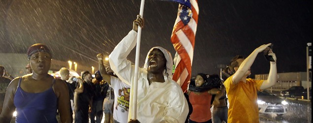 Protesters march in the rain, in Ferguson, Mo., in response to Michael Brown being shot and killed. (Jeff Roberson/AP)