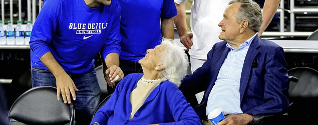 George H.W. Bush at Duke-Gonzaga NCAA tournament game with Cowboys stars. (Getty Images)