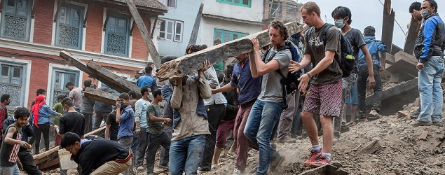 Volunteers in Nepal help remove debris of a building that collapsed after an earthquake near Kathmandu on April 25. (Getty Images)