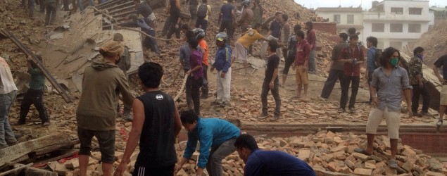 Volunteers help with rescue work at the site of a collapsed building in Kathmandu. (Niranjan Shrestha/AP)