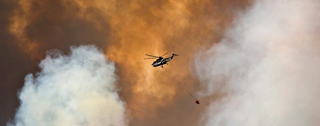 A helicopter battles a wildfire in Fort McMurray, Alta., on Wednesday May 4, 2016. The wildfire has already torched 1,600 structures in the evacuated oil hub of Fort McMurray and is poised to renew its attack in another day of scorching heat and strong winds.THE CANADIAN PRESS/Jason Franson