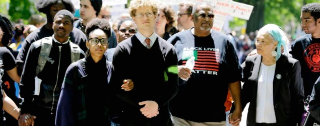 Protesters link arms and hands as they walk near where the county prosecutor lives in Cleveland. (AP)