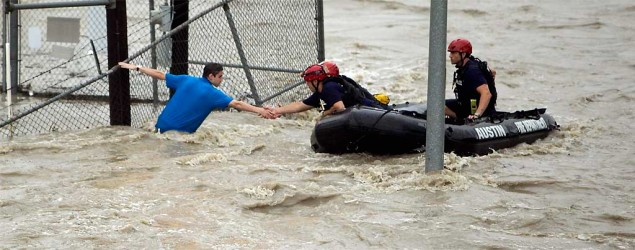 Rescue personnel grab the the hand of a man stranded in rushing water at the northwest corner of Lamar Blvd. and 15th St. in Austin, Texas. (Alberto Martinez/Austin American-Statesman via AP)