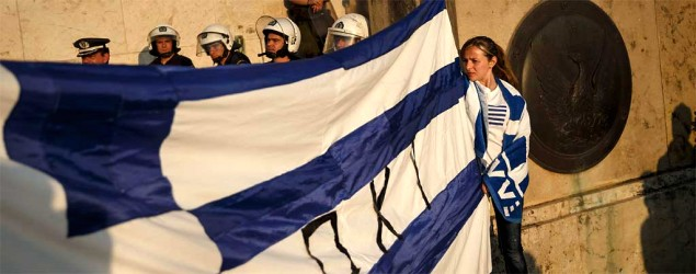 Supporters of the NO vote in the upcoming referendum hold a Greek flag as riot police block the entrance of the parliament in Athens. (Daniel Ochoa de Olza/AP)