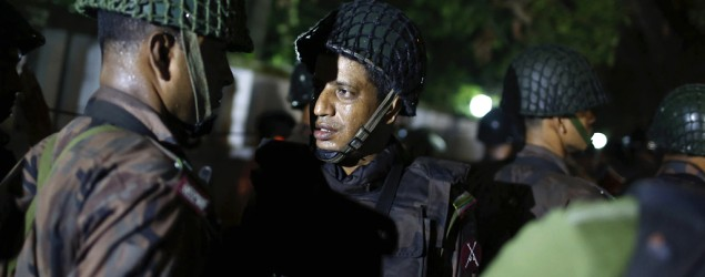 Bangladeshi security personnel stand guard near a restaurant reportedly attacked by unidentified gunmen in Dhaka. (AP)