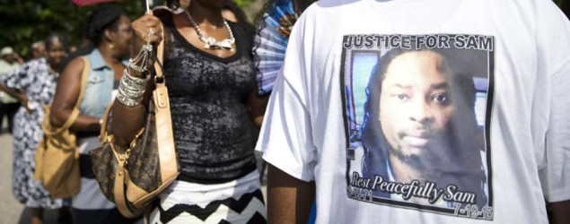 A mourner wears a shirt bearing the likeness of Samuel DuBose, who was fatally shot by a University of Cincinnati police officer who stopped him for a missing license plate. (AP/John Minchillo)