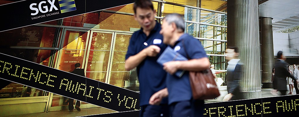 People walk past a logo of the Singapore Stock Exchange (SGX) outside its premises in the financial district of Singapore in this April 23, 2014 file photo.