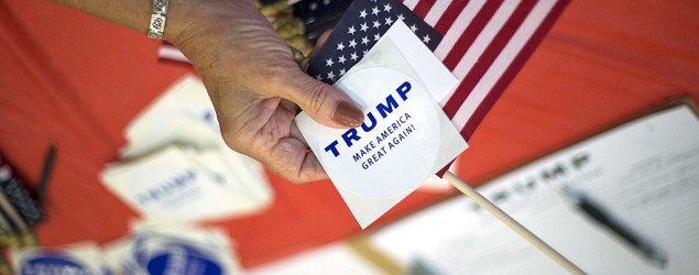 Volunteers hand out flags and stickers before Republican presidential hopeful Donald Trump speaks. (Stephen B. Morton/AP)
