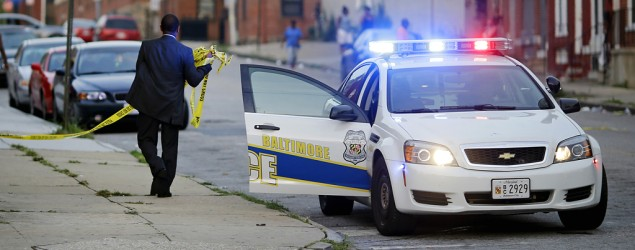 A member of the Baltimore Police Department removes crime scene tape from a corner where a victim of a shooting was discovered. (AP)