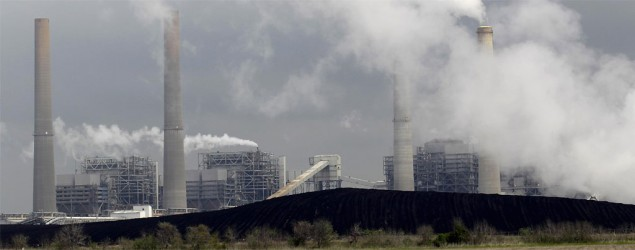Exhaust rises from smokestacks in front of piles of coal in Thompsons, Texas. (David J. Phillip/AP)