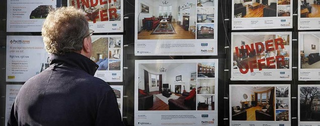 A man looks through the window of an estate agent's in Glasgow (PA)
