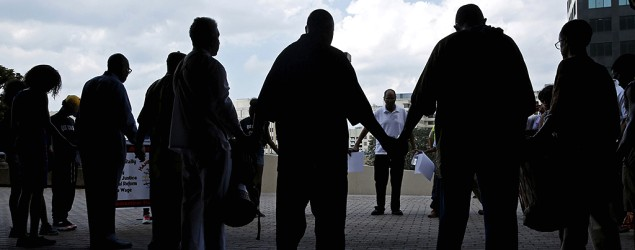 Marchers marking the 10th anniversary of Hurricane Katrina pray at the Mercedes Benz Superdome. (Reuters)