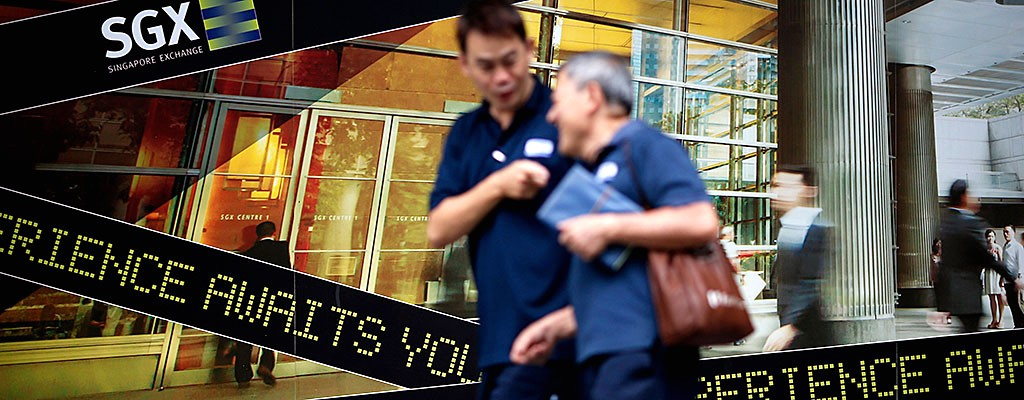 People walk past a logo of the Singapore Stock Exchange (SGX) outside its premises in the financial district of Singapore April 23, 2014. REUTERS/Edgar Su