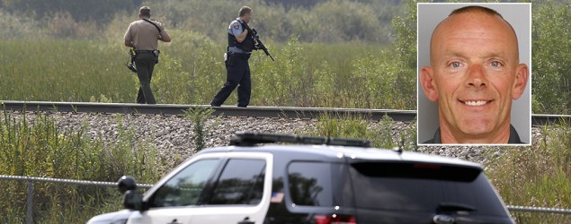 Police officers gather before heading out for a manhunt after an officer was shot in Fox Lake, Ill. (AP)
