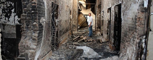An employee of Doctors Without Borders stands inside the charred remains of the hospital. (AP)