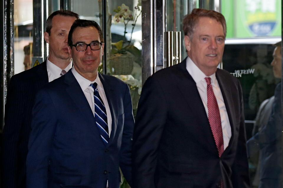 U.S. Treasury Secretary Steven Mnuchin, left, and his Trade Representative Robert Lighthizer arrive at a hotel in Beijing, Thursday, March 28, 2019. Mnuchin and his Trade Representative Robert Lighthizer arrive to China's capital to hold a new round of high-level trade talks with China on March 28-29, start with a working dinner. (AP Photo/Andy Wong)
