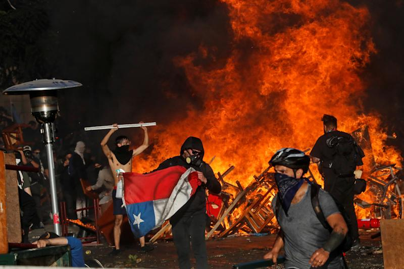 Demonstrators react as fire rages during an anti-government protest in Santiago, Chile on Oct. 28, 2019. (Photo: Henry Romero/Reuters)