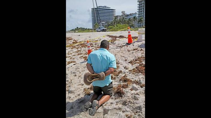 A man prays at the site of the Champlain Towers South condo building collapse in Surfside, Florida, June 25, 2021. The building collapsed early Thursday morning.