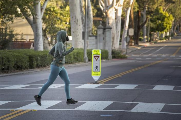 "A jogger in face mask crosses a street at Pomona College on March 27. Due to coronavirus, colleges are making adjustments to things like housing, class sizes and on-campus dining. <span class=""copyright"">(Irfan Khan / Los Angeles Times)</span>"