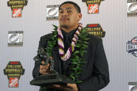FILE - In this Dec. 12, 2019, file photo, Oregon's Penei Sewell poses with Outland Trophy for being the nation's best interior lineman, in Atlanta. Sewell is a likely first round pick in the NFL Draft, April 29-May 1, 2021, in Cleveland.(AP Photo/John Bazemore, File)