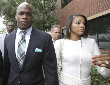 Adrian Peterson arrives at the courthouse with his wife for an appearance Tuesday. (AP)