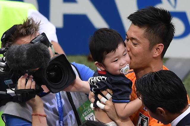 <p>Japan's goalkeeper Eiji Kawashima (R) greets his son Kensei from the crowd after the final whistle during the Russia 2018 World Cup Group H football match between Japan and Poland at the Volgograd Arena in Volgograd on June 28, 2018. (Photo by NICOLAS ASFOURI / AFP) </p>