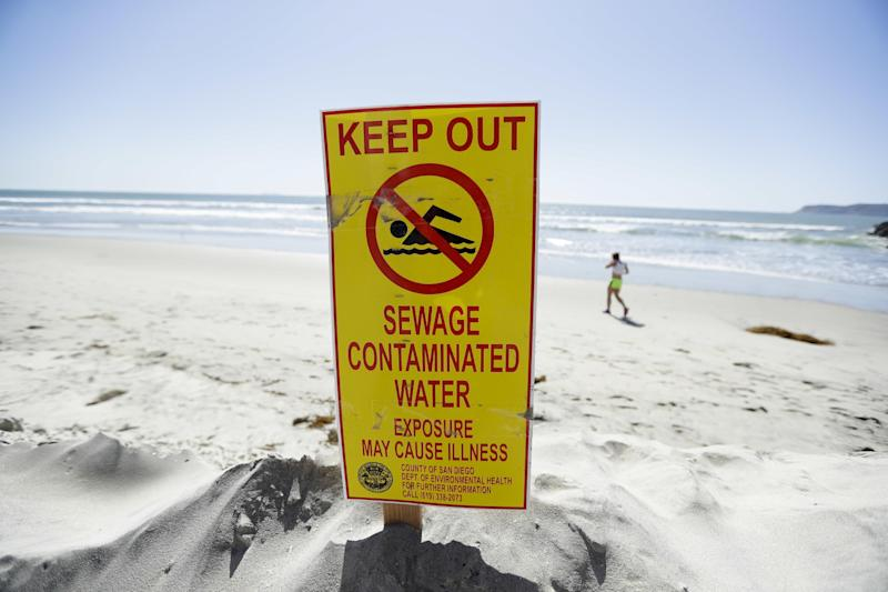 A sign warns of sewage contaminated ocean waters on a beach Wednesday, March 1, 2017, in Coronado, Calif. Coronado and Imperial Beach waters remain closed to swimmers and surfers Wednesday after more than 140 million gallons of raw sewage spilled into the Tijuana River in Mexico and flowed north of the border for weeks in February, according to a report. (AP Photo/Gregory Bull)