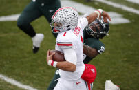 Ohio State quarterback Justin Fields, left, pushes away Michigan State Shakur Brown on a keeper during the first half of an NCAA college football game, Saturday, Dec. 5, 2020, in East Lansing, Mich. Ohio State won 52-12. (AP Photo/Al Goldis)