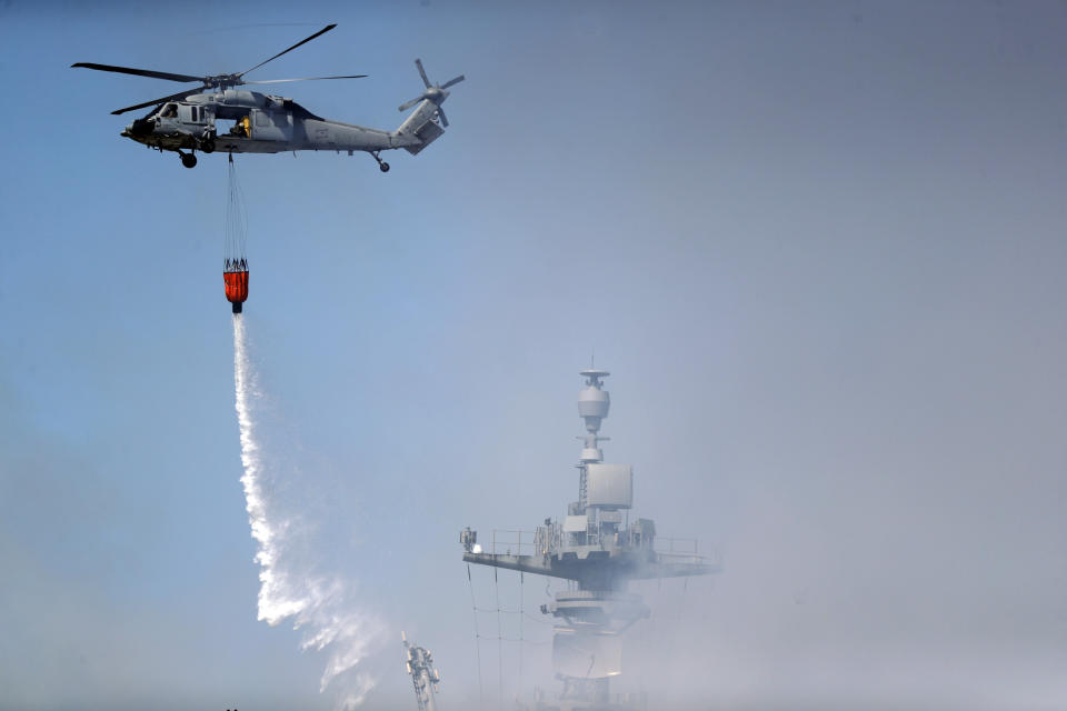 A helicopter drops water on the USS Bonhomme Richard Monday, July 13, 2020, in San Diego. Fire crews continue to battle the blaze Monday after 21 people suffered minor injuries in an explosion and fire Sunday on board the USS Bonhomme Richard at Naval Base San Diego. (AP Photo/Gregory Bull)