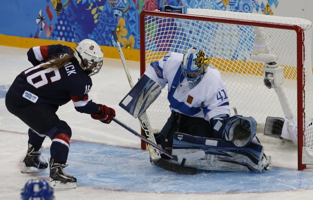 Finland's goalie Noora Raty makes a save on Kelli Stack of the U.S. (L) during the first period of their women's preliminary round hockey game at the Sochi 2014 Winter Olympic Games February 8, 2014. REUTERS/Grigory Dukor (RUSSIA - Tags: SPORT OLYMPICS SPORT ICE HOCKEY)