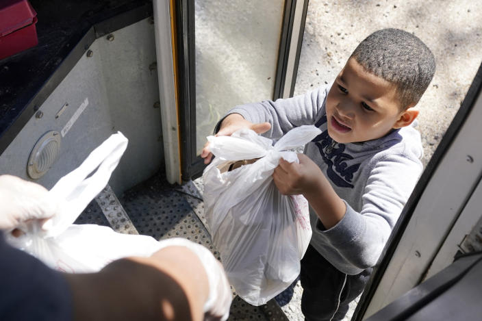 """A Jefferson County School District """"virtual learning student"""" receives several bags with meals, Wednesday, March 3, 2021 in Fayette, Miss. As one of the most food insecure counties in the United States, many families and their children come to depend on the free meals as the only means of daily sustenance. (AP Photo/Rogelio V. Solis)"""