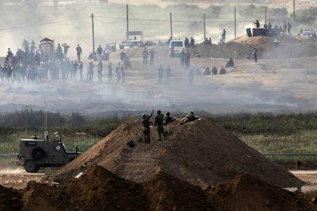 Israeli soldiers are seen next to the border fence on the Israeli side of the Israel-Gaza border, as Palestinians protest on the Gaza side of the border,  Israel April 5, 2018. REUTERS/Amir Cohen