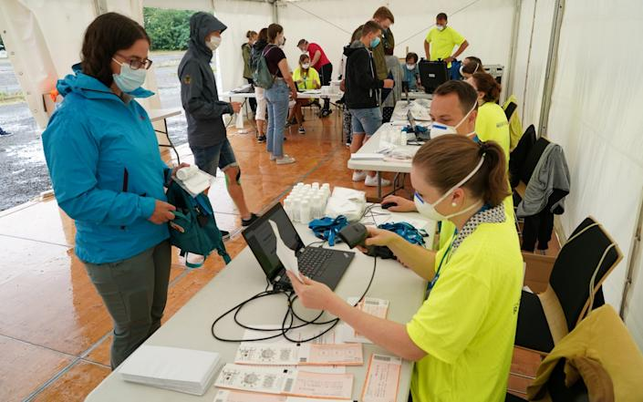 Participants register to take part in the RESTART-19 Covid transmission risk assessment study at an indoor arena - Sean Gallup / Getty