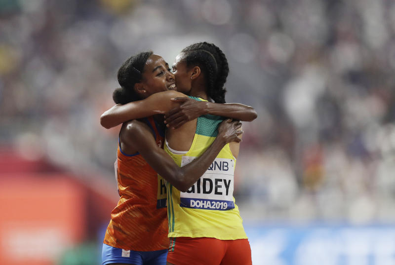 Sifan Hassan, of the Netherlands, left, celebrates with Letesenbet Gidey, of Ethiopia, after winning the gold in the women's 10,000m final at the World Athletics Championships in Doha, Qatar, Saturday, Sept. 28, 2019. (AP Photo/Petr David Josek)